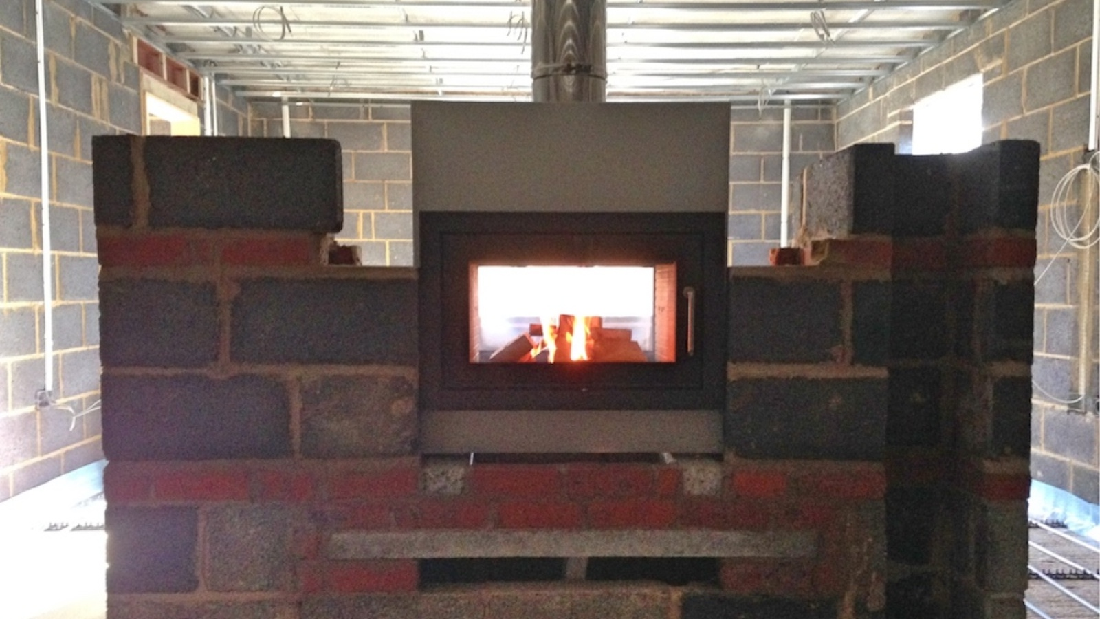 With the flue and stove installed, the builder can continue their works.