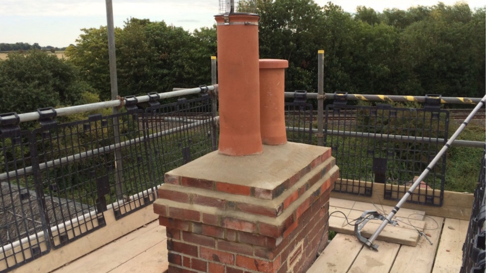 A newly extended chimney stack to a thatched cottage with one capped redundant chimney and one open to the wood burner below.