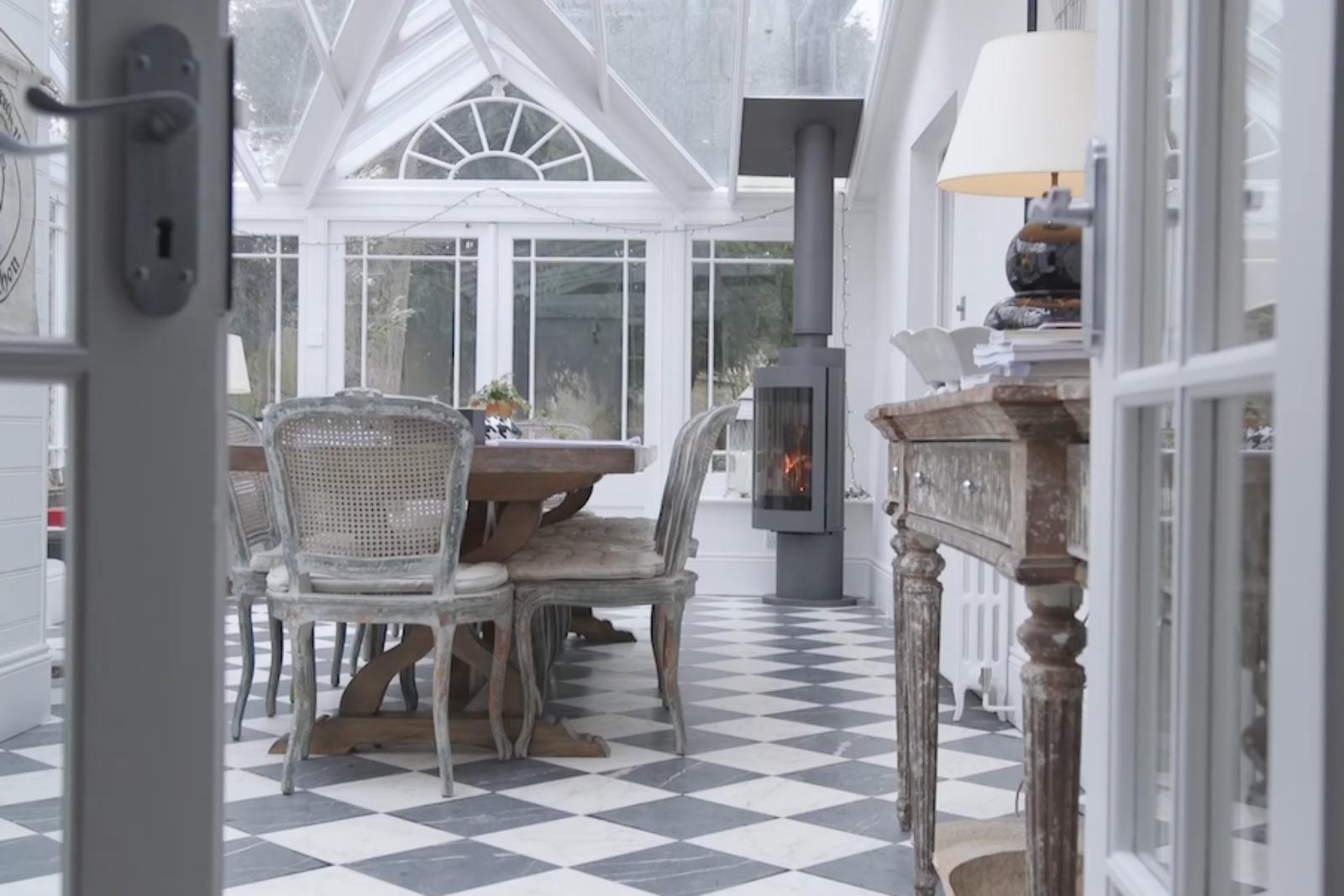 The conservatory dining room with Harrie Leenders slim Cylon log burner.