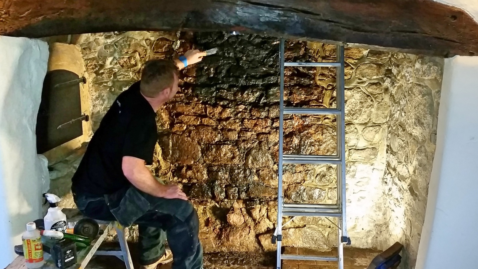 Cleaning stonework in a listed thatched cottage.