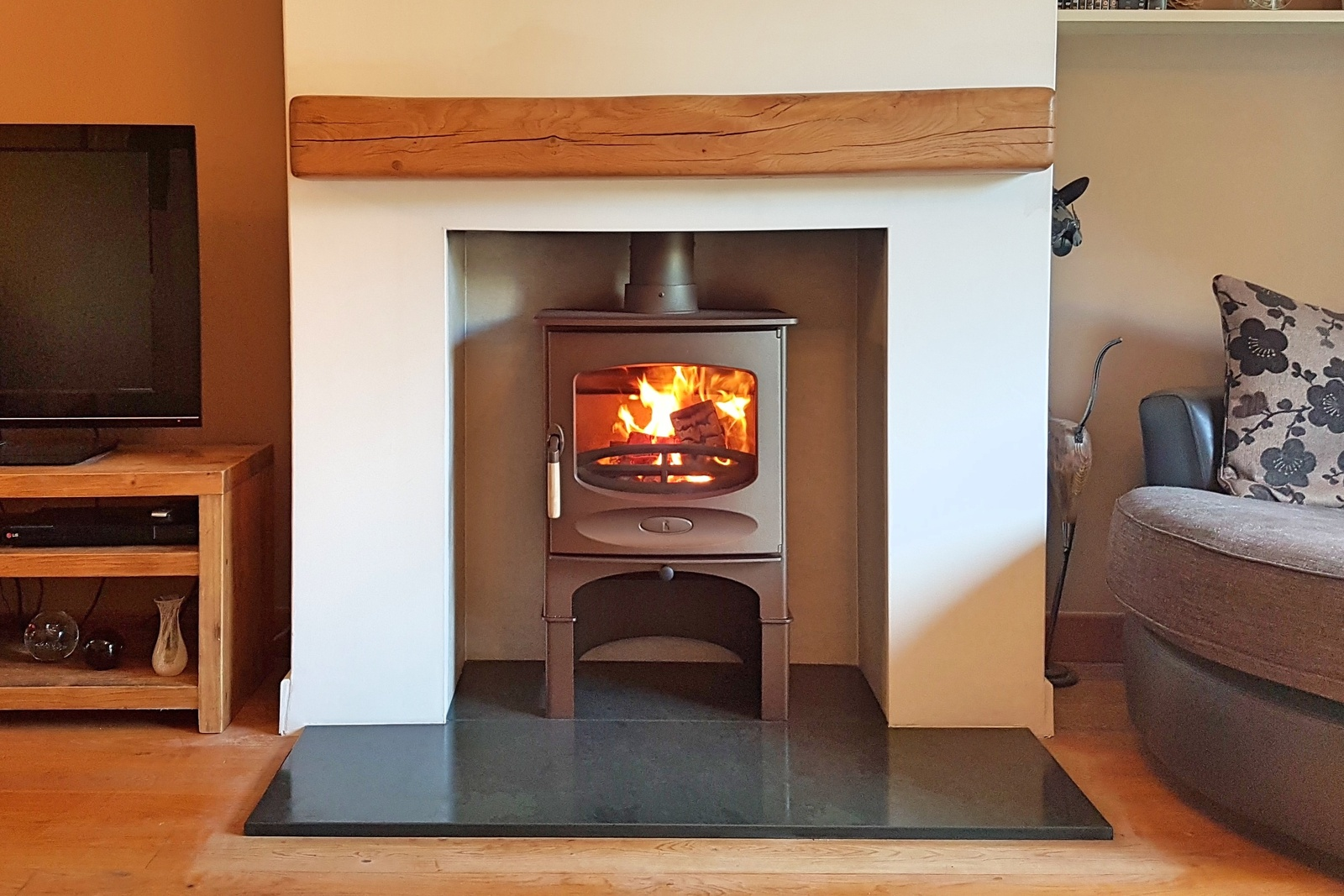The stove was chosen in a warm bronze colour to sit beautifully with the rustic wooden fireplace beam