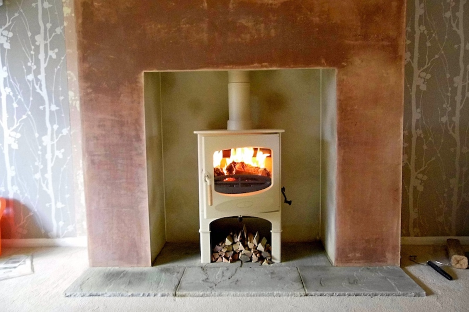 The original fireplace had been removed in this 1950s semi. A faux chimney breast was created with rustic stone hearth and a Charnwood C-Five in an Almond colour to lighten the room