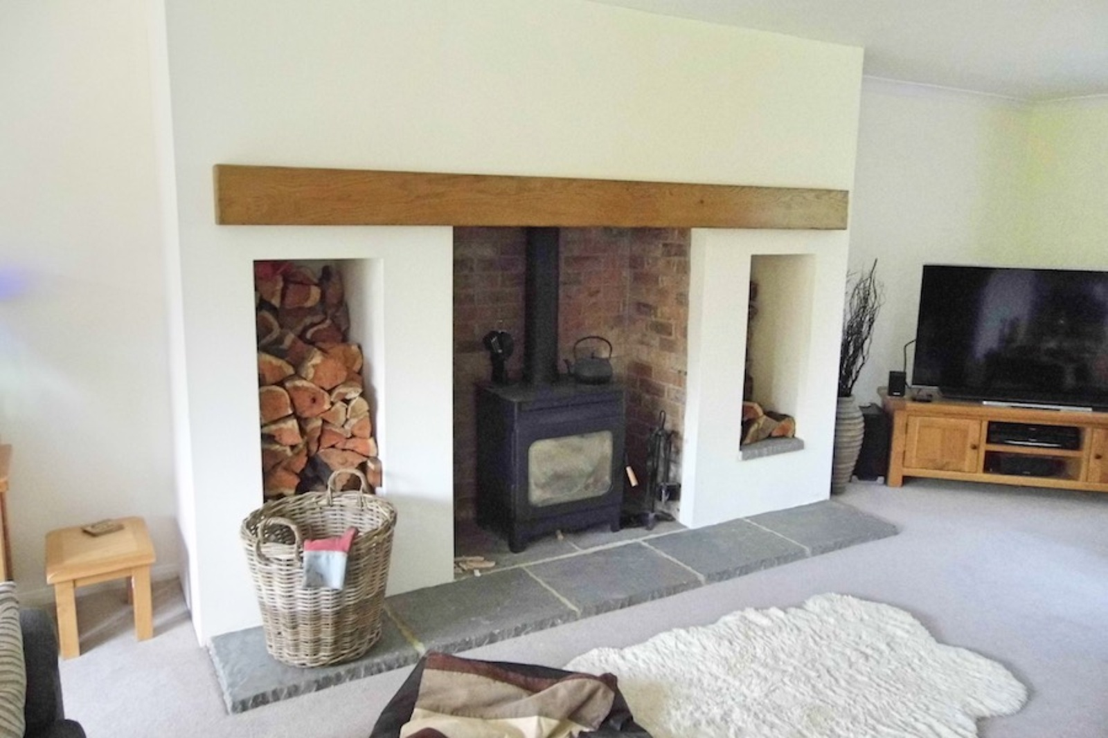 A delicate colour choice and a warm wood finish to the inglenook beam creates a fresh modern feel to a new faux fireplace.