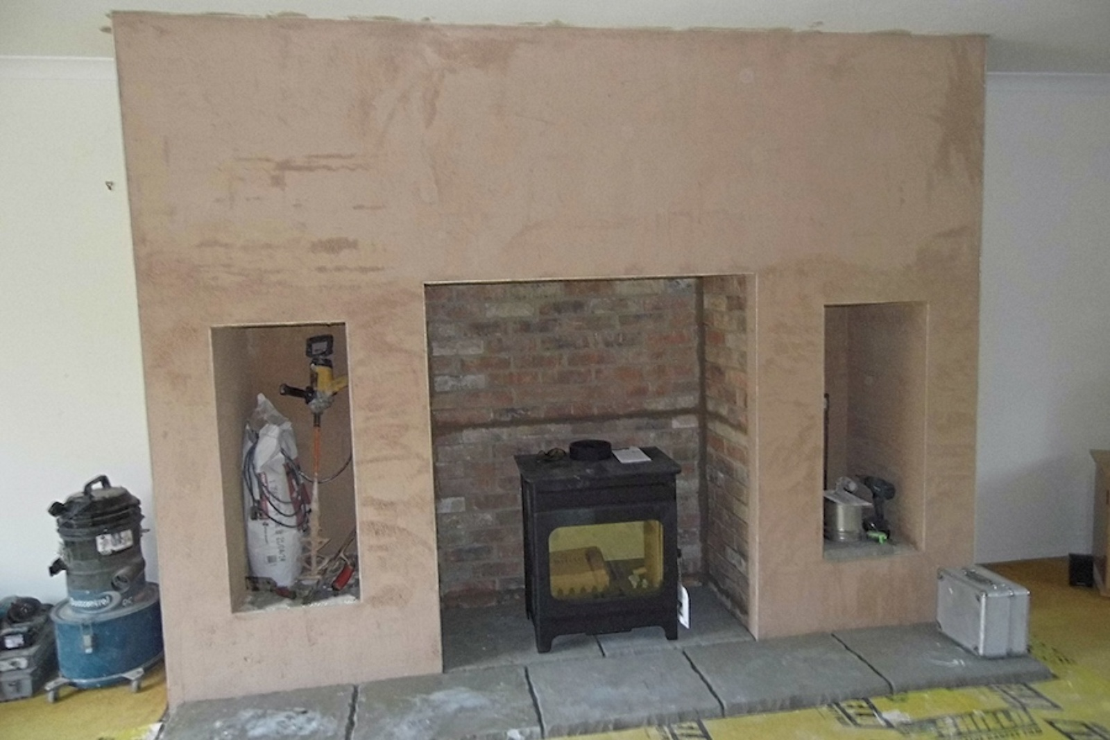 A new flagstone hearth has been laid and the stove placed ready for connecting to the lined chimney.